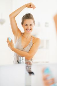 25078415 - smiling young woman applying deodorant on underarm
